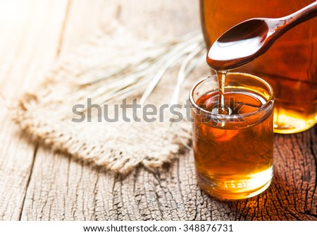 maple syrup in glass bottle on wooden table - stock photo