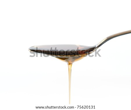 Maple Syrup Overflowing Off A Silver Dessert Spoon - stock photo