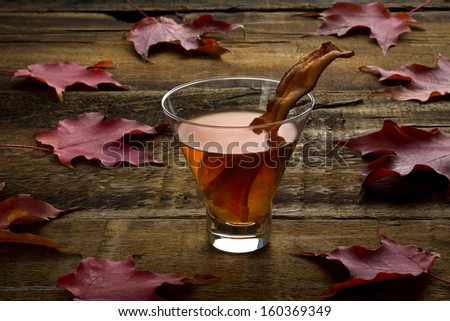 Maple whiskey bacon cocktail  on rough wood and maples leaves - stock photo