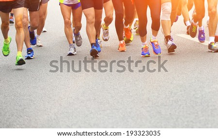 marathon athletes competing in fitness and healthy active lifestyle feet on road  - stock photo