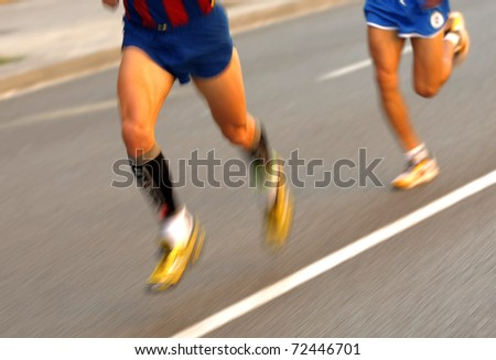 Marathon runner legs on the road followed by another runner with panning blur - stock photo