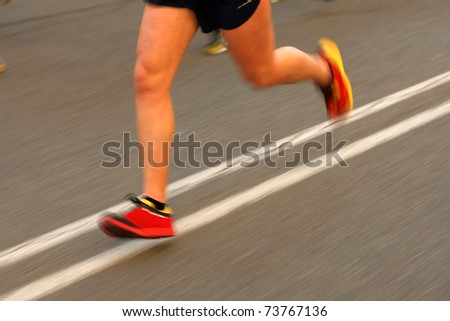 Marathon runner legs on the road with panning blur - stock photo