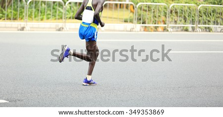 Marathon runner running on city road