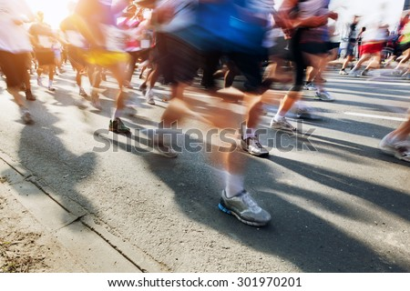 Marathon runners in motion. Running in the city, sun shining. - stock photo