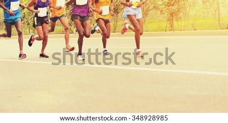 Marathon runners running on city road - stock photo