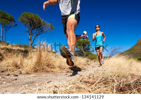 marathon running athletes couple training on trail fitness sport active lifestyle - stock photo