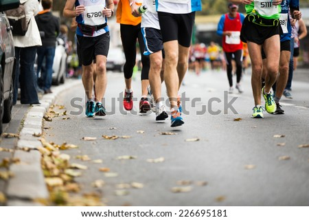 Marathon running race, people feet on autumn road - stock photo