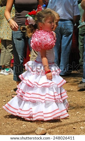 MARBELLA, SPAIN - JUNE 8, 2008 - Young girl in a flamenco dress at the Romeria San Bernabe, Marbella, Costa del Sol, Malaga Province, Andalusia, Spain, Western Europe, June 8 2008. - stock photo