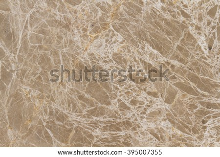 Marble Emperador Light. The surface of natural stone beige and light brown shades with hints of golden light covered with a homogeneous network of thin veins. - stock photo