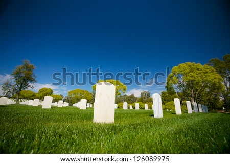Marble headstones mark the final resting place of American veterans in Los Angeles National Cemetery. - stock photo