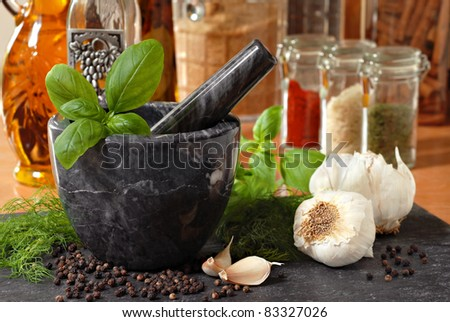 Marble mortar and pestle with fresh basil, dill, garlic, and peppercorns on slate cutting board.  Assorted spices and oils in soft focus in background.  Macro with shallow dof. - stock photo