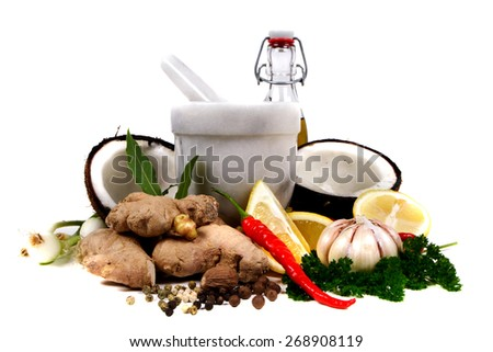 Marble pestle and mortar with herbs, chili, coconut and ginger - stock photo