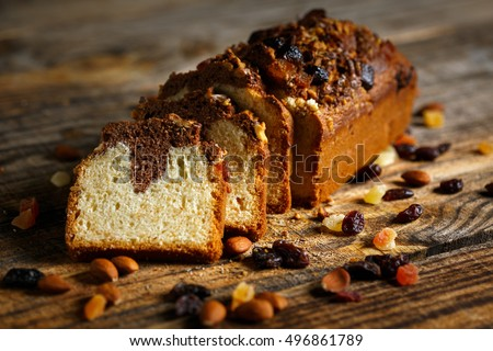 Marble pound cake with candied almonds and cranberries on a wooden board