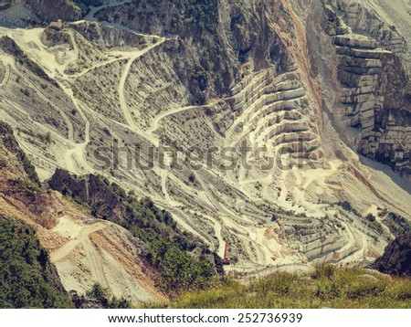 Marble quarry, Carrara, Italy. Truly vast! Machinery below gives sense of scale. Retro filtered image. - stock photo