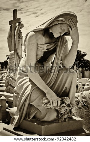 marble sculpture of a sad woman on a grave with a cemetery in the background - stock photo
