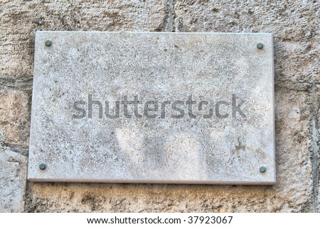 marble sign on the old stone wall - stock photo