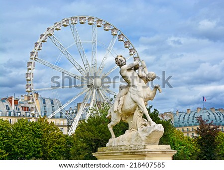 Marble statue and ferriw whell in Tuileries Garden (Jardin des Tuileries). Is  public garden located between Louvre Museum and Place de la Concorde in Paris, France - stock photo