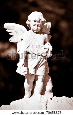 Marble statue of a child angel in sepia with a diffused background - stock photo
