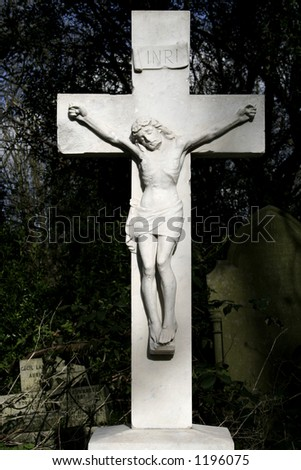 Marble statue of Jesus on cross at old Graveyard - stock photo