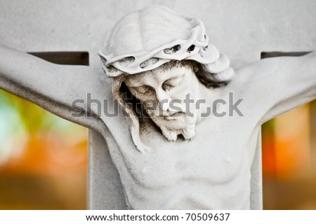 Marble statue of the crucifixion of Jesus with a colorful out of focus background - stock photo