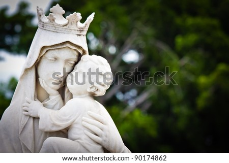Marble statue of the virgin Mary carrying a baby Jesus with a diffused vegetation background