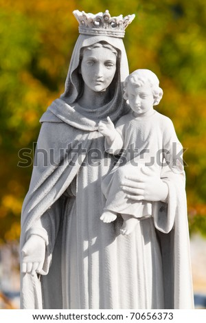 Marble statue of the virgin Mary carrying a child with a diffused vegetation background - stock photo