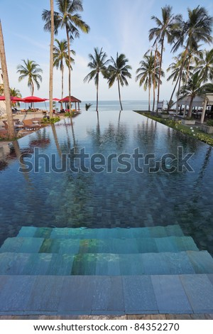 Marble steps leave under pool water. A beach on coast of the Thai gulf, red beach umbrellas, plank beds and palm trees against the sea