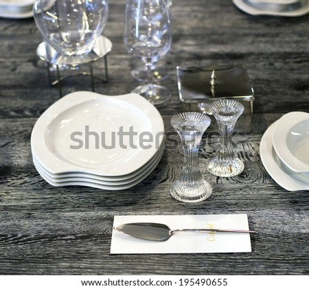marble table with plates and glasses and candlesticks - stock photo