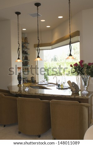 Marble topped kitchen counter with armchairs in modern house - stock photo