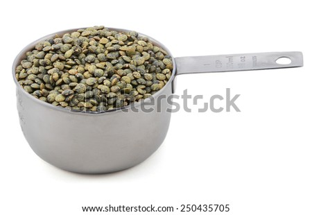 Marbled dark green lentils in an American cup measure, isolated on a white background - stock photo