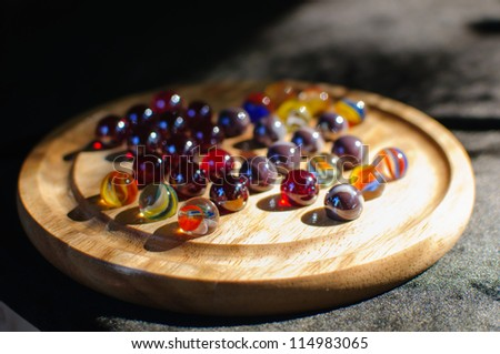 Marbles are spherical glass toys used to play a variety of different games. - stock photo