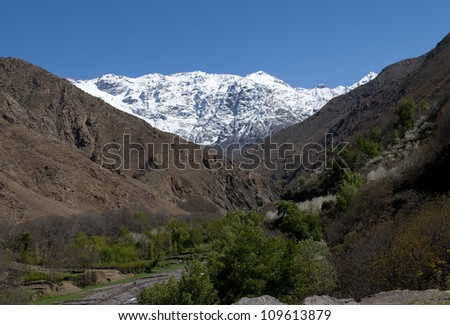 March 2012. In the Atlas Mountains. Morocco with snow on the tops seen through a green arable valley with brown hill sides - stock photo