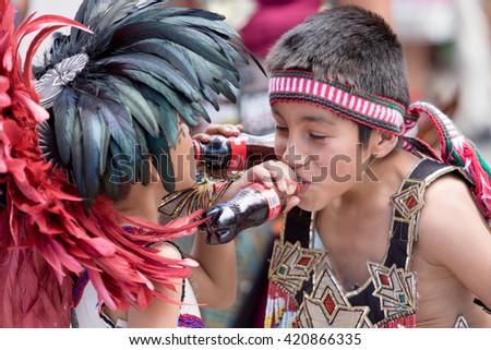 March 4, 2016, San Miguel de Allende, Mexico: indigenous boys in traditional clothing drinking Coca Cola at  the Senior de la Conquista celebration - stock photo