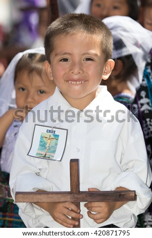 March 25, 2016 San Pedro la Laguna, Guatemala: a young mayan boy holding a wooden cross during Easter Holy week celebration