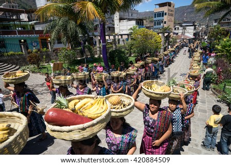 March 23, 2016 San Pedro la Laguna, Guatemala: mayan tzutujil women lining up with fruit baskets on their head to enter the local church on easter holy week celebration