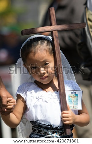 March 25, 2016 San Pedro la Laguna, Guatemala: young mayan girl dressed in traditional clothes holding a wooden cross at Easter procession