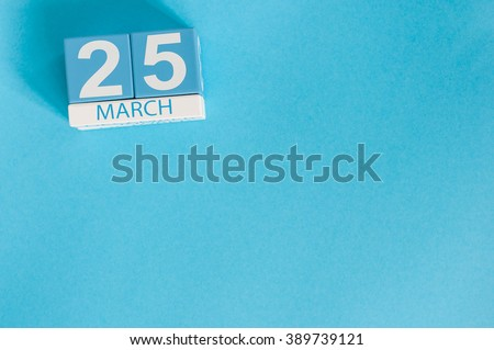 March 25th. Image of march 25 wooden color calendar on blue background.  Spring day, empty space for text. - stock photo