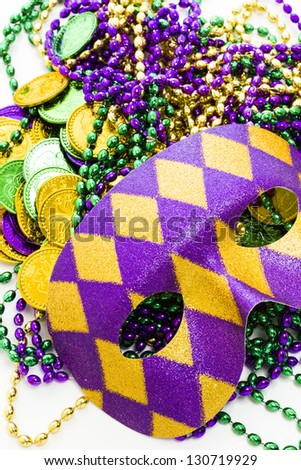 Mardi Gras beads and colorful masks on white backgound. - stock photo