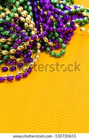 Mardi Gras beads yellow backgound. - stock photo