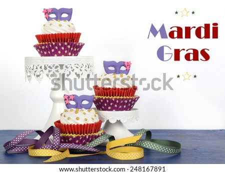 Mardi Gras cupcakes with purple mask toppers on rustic style dark blue vintage wood table. - stock photo