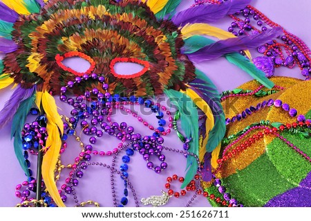 Mardi Gras feathered mask and top hat with Mardi Gras beads still life in gold green purple yellow and red on lilac background part of a series.  - stock photo