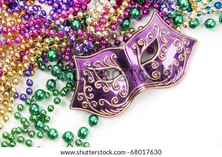 Mardi gras mask and beads in pile - stock photo