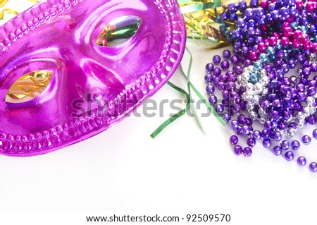 mardi gras mask and beads on white