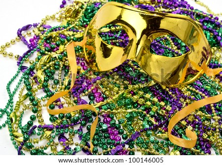 Mardi Gras masquerade mask on a background of colorful Mardi Gras Beads - stock photo