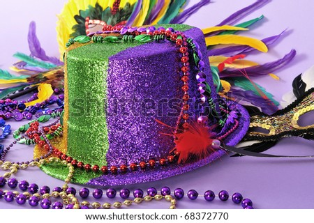 Mardi Gras or New Year party hat feathered masks and Mardi Gras beads. Close up studio shot on purple background.  Set series. Also for New Year's Eve. - stock photo