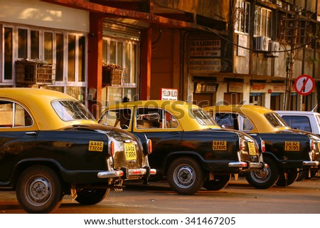 MARGAO, INDIA - NOVEMBER 20, 2007: Yellow & black Ambassador cars at the cab-stand in the state of Goa  - stock photo