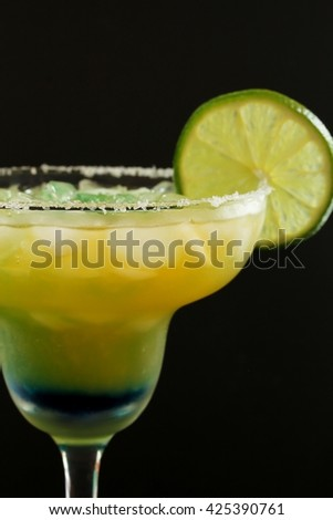 Margarita cocktail with lime against black background /Green Margarita, selective focus - stock photo