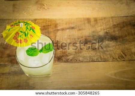 margarita cocktail with salty rim on wooden table with limes and mint - stock photo