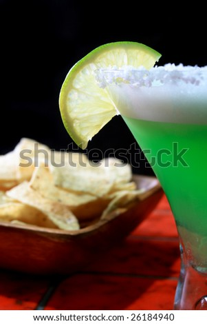 Margarita drink on bar counter with nacho tortilla chips in background - stock photo