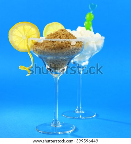 Margarita glasses with lump, brown sugar, cocktail cherries and citrus slices on blue background - stock photo